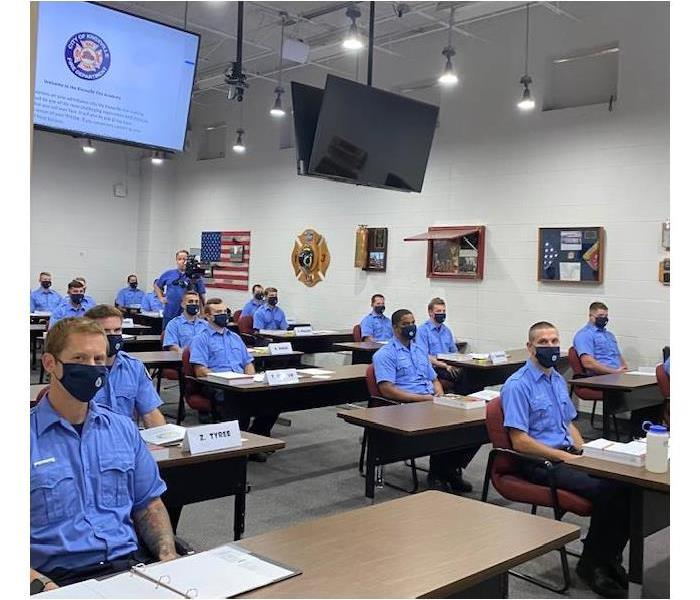 People in blue shirts sitting at wood desks