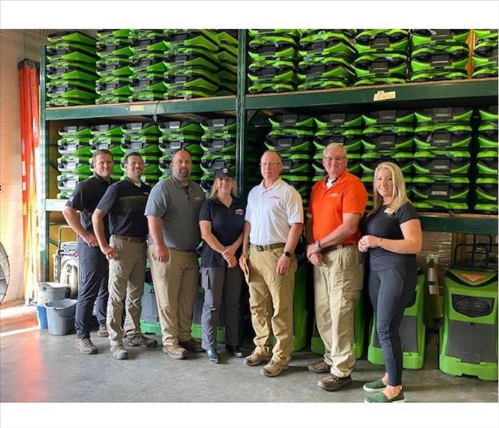 Owners plus key employees posing in the warehouse with air movers in the background