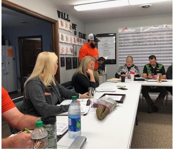 SERVPRO employees attending weekly meeting.  Sitting around tales while man addresses group