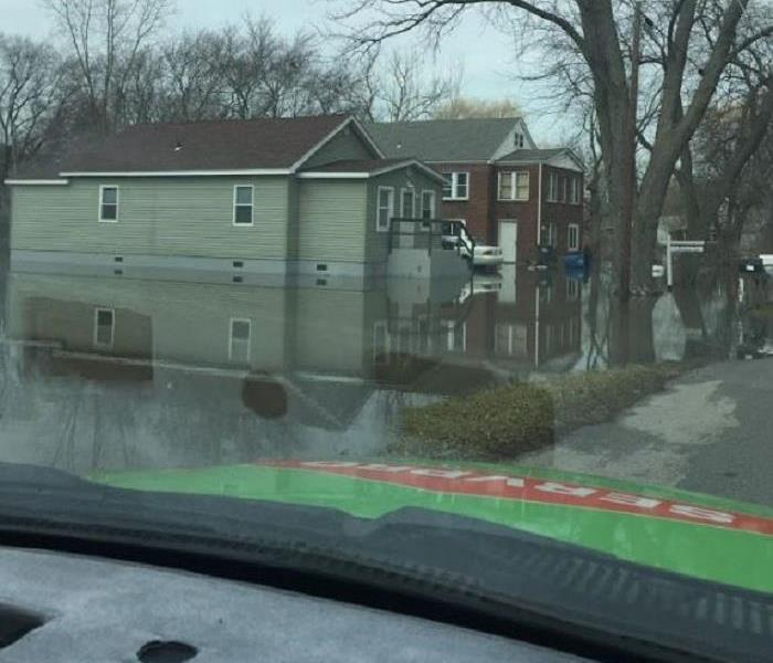 Flooded roads and yards; water surrounding homes and entering homes
