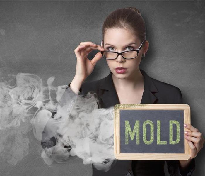 female holding a mold sign