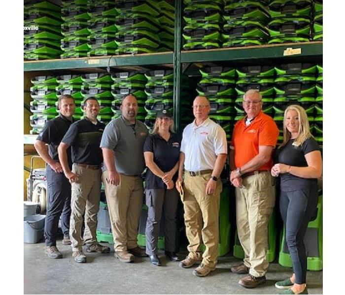 SERVPRO team members standing in front of stacked SERVPRO restoration equipment in a storage facility
